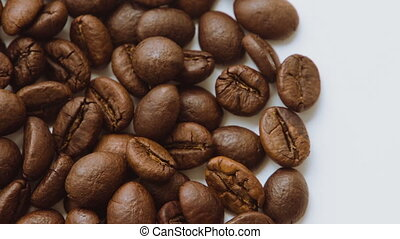 A pile of roasted coffee beans rotating. Close up