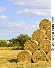 a pile of round bales in a field in summer