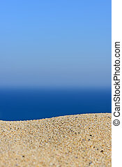 A pile of sand on a beach against the sea and sky. Ready for product display montage