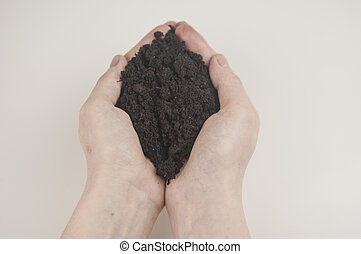 A pile of soil in female hands.
