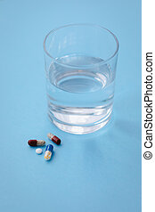 A pile of tablets on blue background with a glass of water, ready to be taken, medicine drugs concept