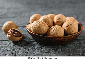 A pile of walnuts in a clay bowl on a dark wooden table.