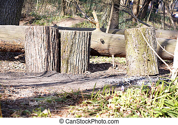 A pile of wooden logs on the ground. Wooden obsolete log, firewood.