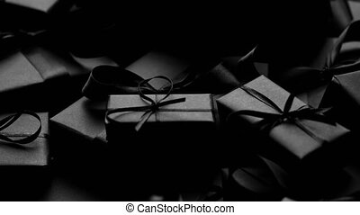 A pile various size black boxed gifts placed on stack. Christmas concept. Dark mood and style. Top view, flat lay.