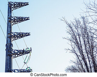 A pillar with electric wires in front of tree branches against the blue sky