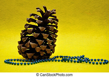 A pine cone on a yellow background and blue beads