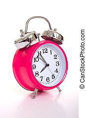 A pink alarm clock on a white background