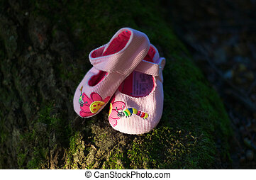 a pink baby shoes in a green natura