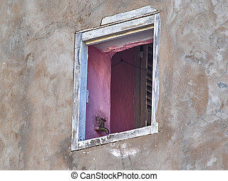 A pink window opening on a gray wall, in the slope of the window is attached a copper water tap, an unusual interior design of the walls.
