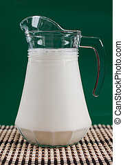 A pitcher of milk and a glass