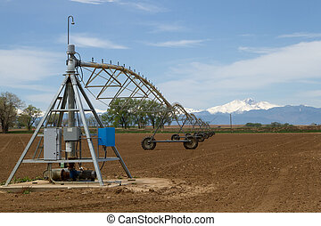 A Pivot Irrigation System in a farming field with Longs Peak Mountain in the background on a sunny day