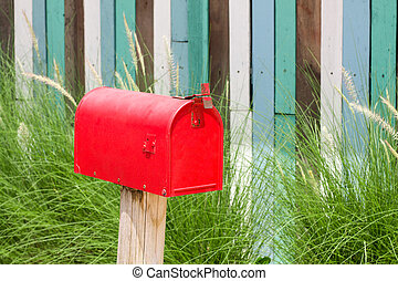 Mailbox - A plain Red Mailbox  in front of some bushes.