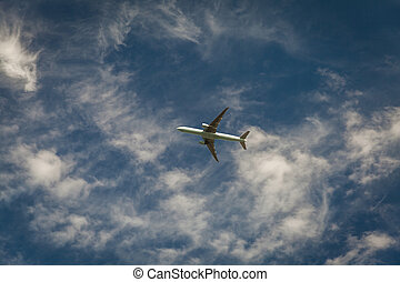 A plane flying blue sky with clouds in the background