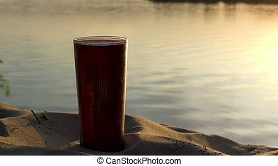 A plastic cup of coffee on a lake bank at a nice sunset in summer