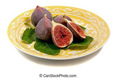 a plate figs on a fig leaf - fresh figs arranged on a plate,...