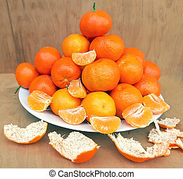 A plate full of clementines on a wooden background