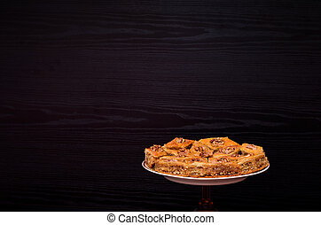 A plate of baklava with honey on a black background, traditional Turkish sweets. Rombus