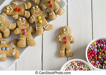 A Plate of Decorated Gingerbread Men with Bowls of Chocolate Buttons and Sprinkles on the Side for Decorating
