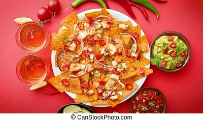 A plate of delicious tortilla nachos with melted cheese sauce, grilled chicken, jalapeno peppers, red onion, tomato, guacamole dip and spicy salsa. With cold sparkling beer. Placed on red background
