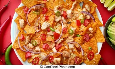 A plate of delicious tortilla nachos with melted cheese sauce, grilled chicken