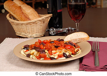 A plate of pasta puttanesca with wine and bread