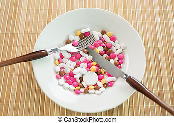 a plate of pills on a wooden table