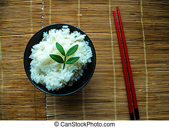 a plate of rice and chopsticks