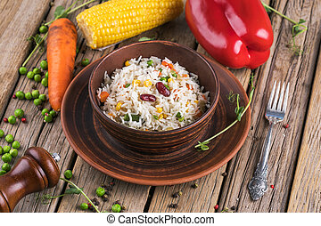 A plate of rice with vegetables on wooden boards