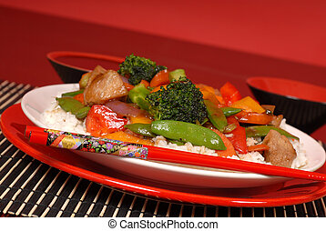 A plate of stir fry pork with chop sticks in a red theme