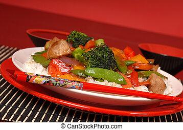 A plate of stir fry pork with chop sticks