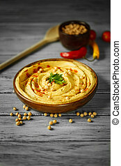 A plate with hummus with leaves of parsley, a bowl of chickpeas, cherry tomatoes on a blurred gray background.