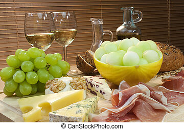 A platter of Mediterranean food including cheese, grapes, ...