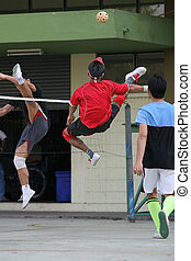 A player volleys the ball over the net in Sepak Takraw (Kick Volleyball). The game is a cross between soccer and volleyball; and is a fast-growing and popular sport in Asia