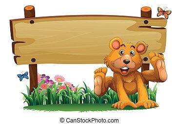 A playful bear near the empty wooden signboard