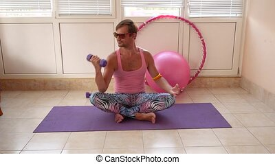 A playful handsome guy in a pink T-shirt and blue leggings is engaged in fitness depicting a girl. Slow motion