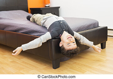 Playful little boy in bed upside down