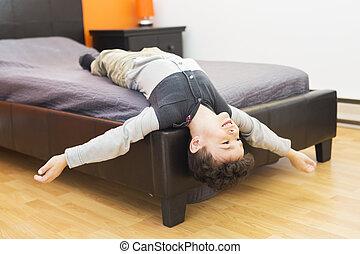 Playful little boy in bed upside down