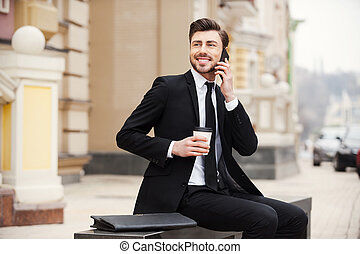 A pleasant escape from the office. Confident young man in formalwear holding mobile phone and cup of coffee while sitting outdoors