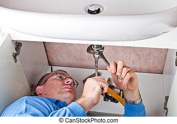 a plumber repairing a broken sink in bathroom