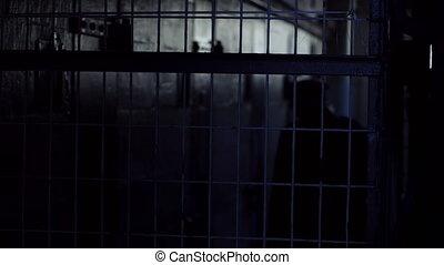 A police man lurking inside a jail shot - A medium shot of a...