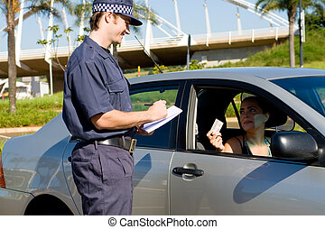 speeding ticket - a police officer handing a woman in car a...