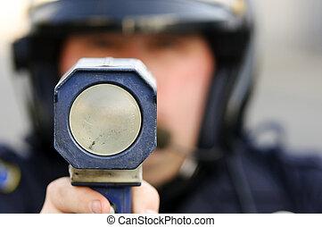 radar gun - a police officer pointing his radar gun at...