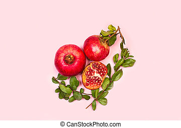 A pomegranates with branches and leaves on a pink background and with copy space