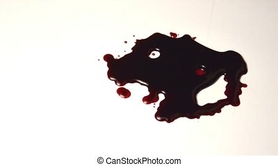 A pool of blood on the floor. blood drips