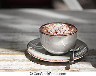 A porcelain cup of black coffee with white marshmallows on a shabby wooden background. A cocoa drink in a clay mug. Copy space.