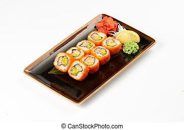 A portion of maki sushi with an assortment of Japanese side dishes in a rectangular ceramic plate on a white plate.