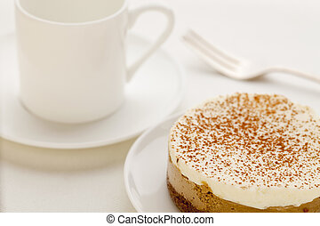 a portion of mocha cheesecake on white china plate with a cup of espresso coffee