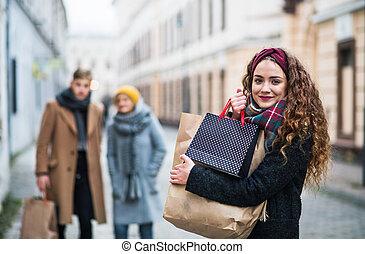 a, porträt, von, teenagermädchen, mit, papier, einkaufstüten, straße, in, winter.