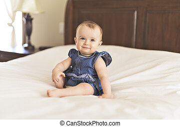 Portrait of a baby on the bed in her room