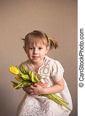 A Portrait of a beautiful little girl with a bouquet of yellow tulips flowers